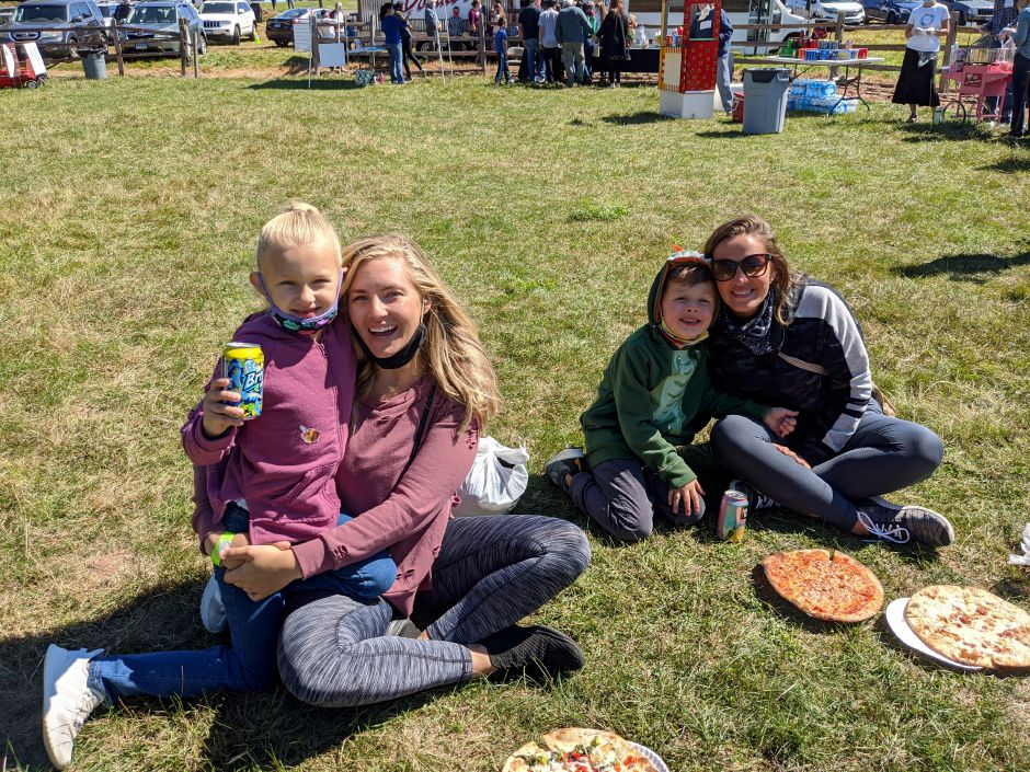 Seven-year-old Riley Maloney, left, enjoys lemonade and pizza with her mother, Megan Eustace, along with Jessica Stark and her son Dimitri, 5, during Saturday's Family Fun Fest at Hickory Hill Orchard.