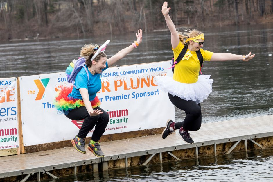 Southington YMCA registrars Amber Knight, left, and Emily Snow, right, jump into the frigid water during the 15th annual Sloper Plunge, in Southington, January 18, 2020. The event by the Southington-Cheshire Community YMCAs raises money for local kids to attend camp. Photo by David Torrellas, special to the Record-Journal.