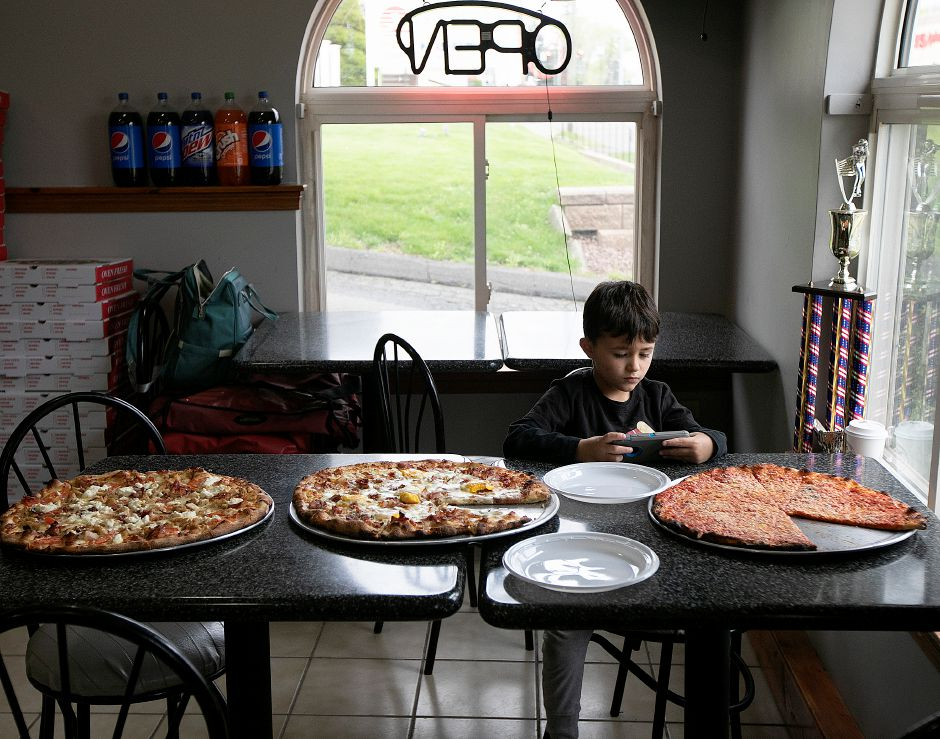 Madden Laudano, 5, plays a game next to pizzas at Laudano