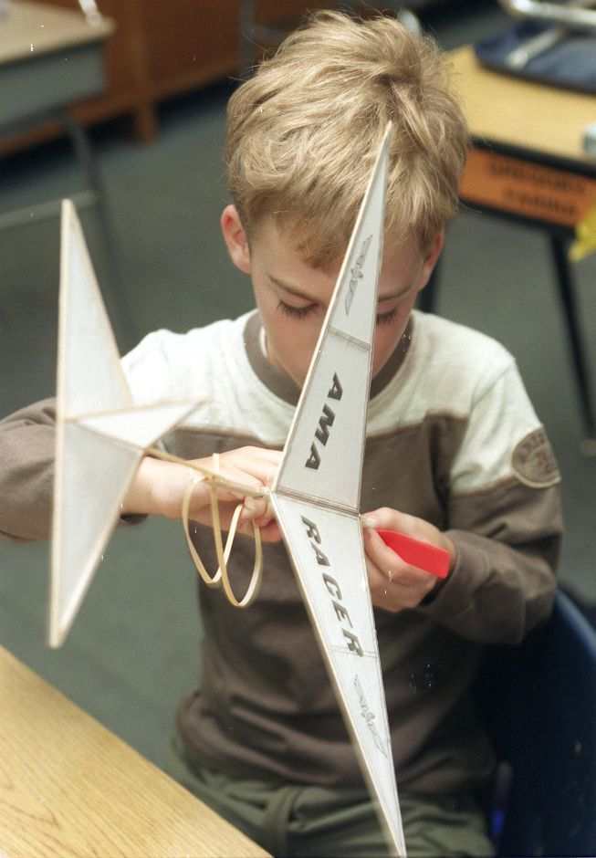 Gregory Wright attaches a large rubber band to the model airplane he made at Cook Hill School in their after school enrichment program, Wed., March 29, 2000.