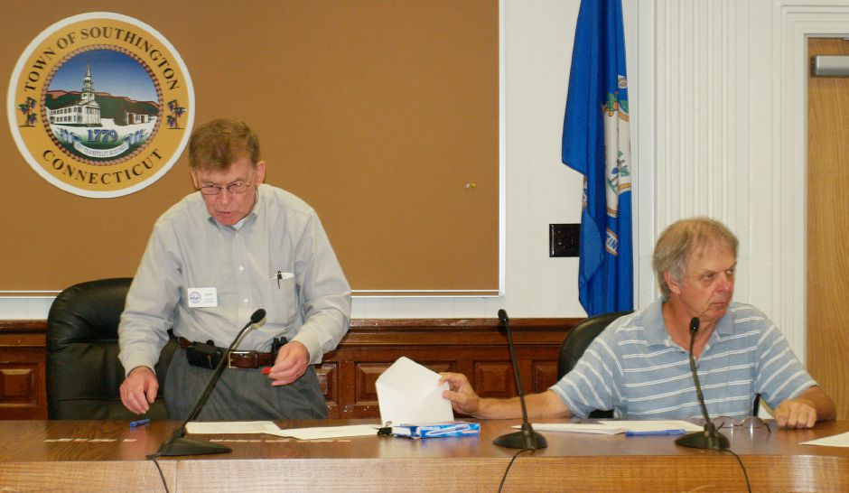 Republican Registrar of Voters Edward Malczyk, right, holds an envelope for Robert Sherman, Democratic registrar of voters, in 2011 in the Council Chambers of Southington Town Hall. File photo, Record-Journal