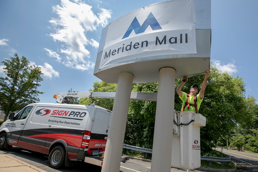 Spencer Browne, a worker for Southington-based Sign Pro, takes measurements for new signage after attaching a temporary sign at the north entrance of the newly named Meriden Mall in Meriden Thursday. Dave Zajac, Record-Journal