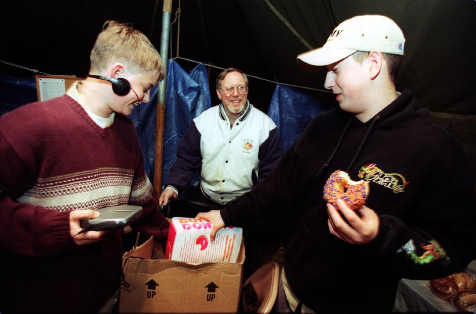 "Boy Scouts Dan Shoemaker, 13, left, and Jeff Tranquist, 15, right, help parent Luke McLoughlin, center, unload boxes of donuts donated by a local Dunkin Donuts store just after midnight, Friday, April 21, 2000 at their annual Easter weekend ""Coffee Break"" at the I-91 southbound rest area in Wallingford. They will be manning the tent through Sunday, and they are from Troop 4."