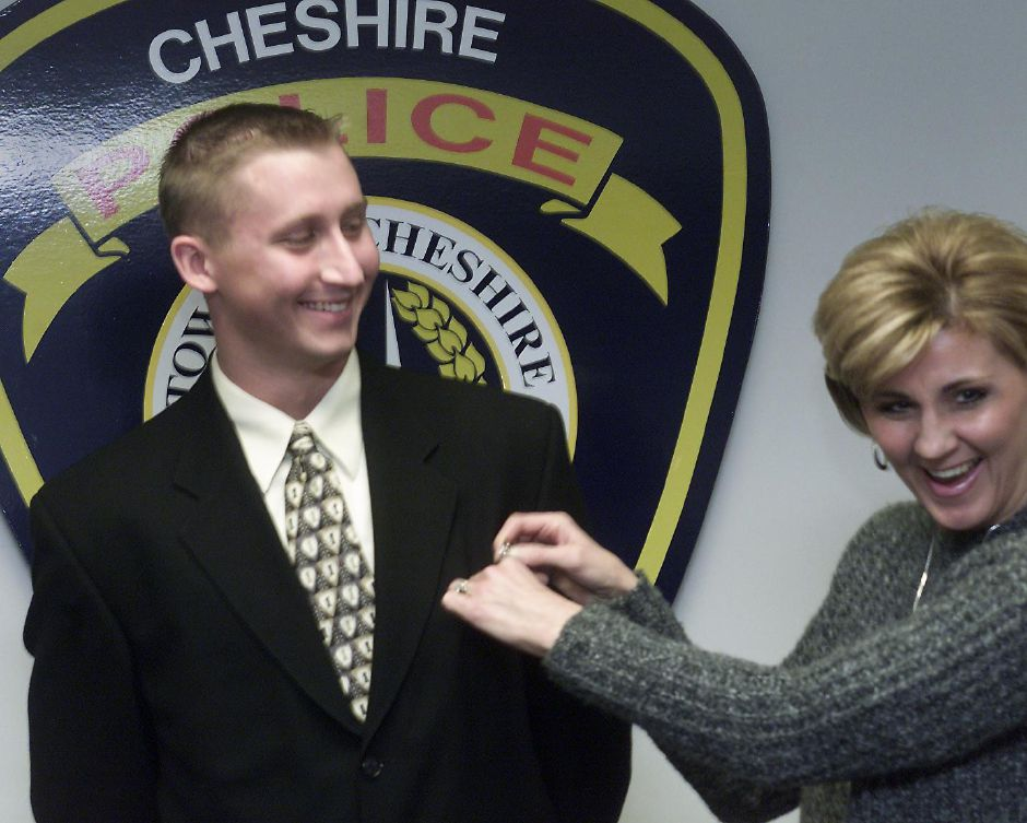 Steve Jester has his police badge pinned on by his mother Cheryl Jester at the Cheshire Police Department.  Jester begins at the police academy in Meriden on Friday January 5, 2001.