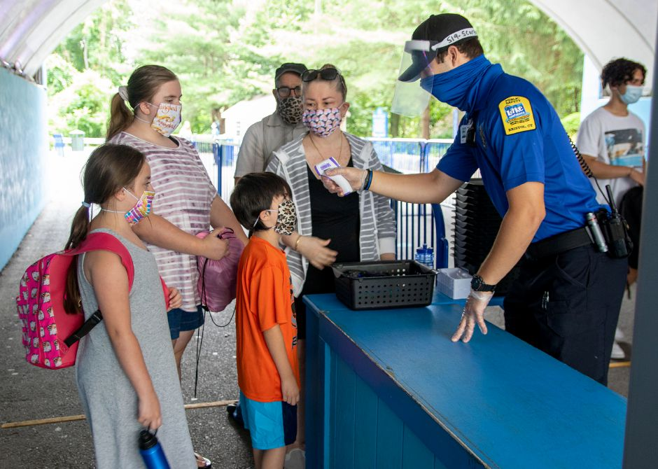 Lake Compounce safety officer Joseph Scarpati takes the temperature of Santino Voltaggi, 8, of Carmel, N.Y.  before he entered the park with his family on Tuesday.