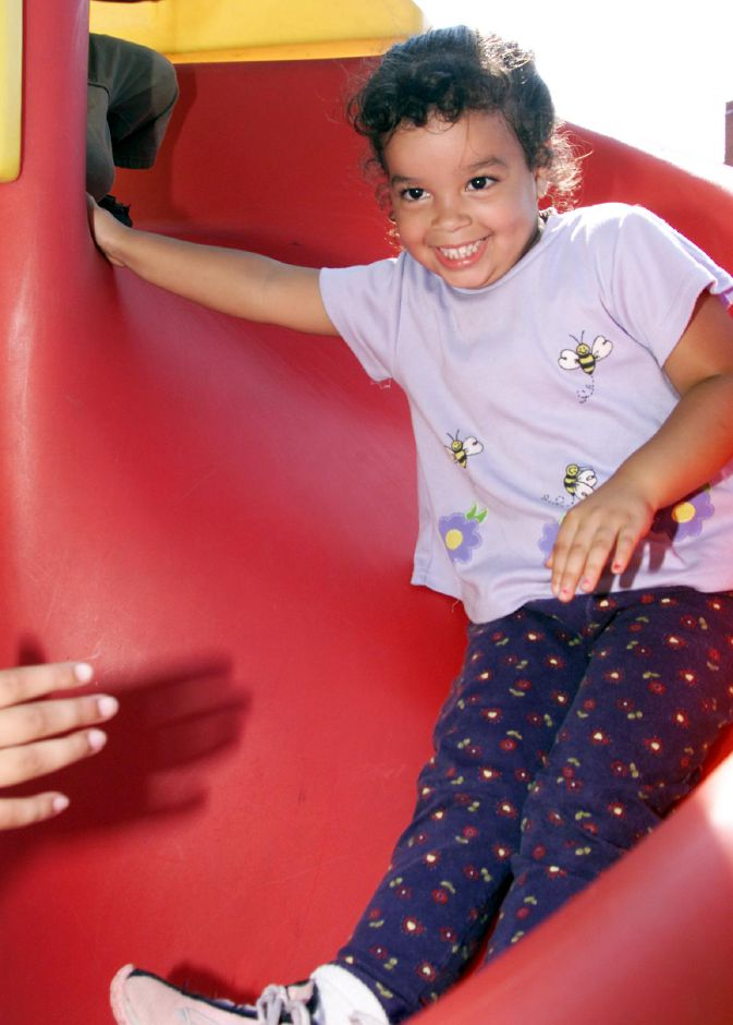 Ivelese Davila, 3, slides down one of the slides at the new Chamberlain Heights playground Tues., Aug. 15, 2000.