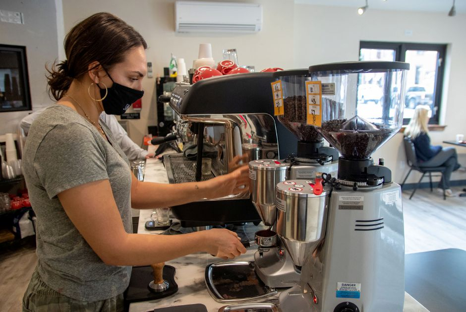 Barista Kaylea Mazzamurro makes a latte at the Lions Den Coffee Shop in the Plantsville section of Southington. The shop opened on Nov. 1, 2020. Aaron Flaum, Record-Journal