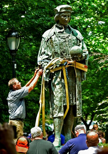 FILE- In this June 24, 2020 file photo, a worker prepares to remove the statue of Christopher Columbus from Wooster Square Park, in New Haven, Conn. Disputes over what to do with statues of Christopher Columbus in Connecticut have resulted in both civil and criminal complaints. (Peter Hvizdak/Hearst Connecticut Media via AP)