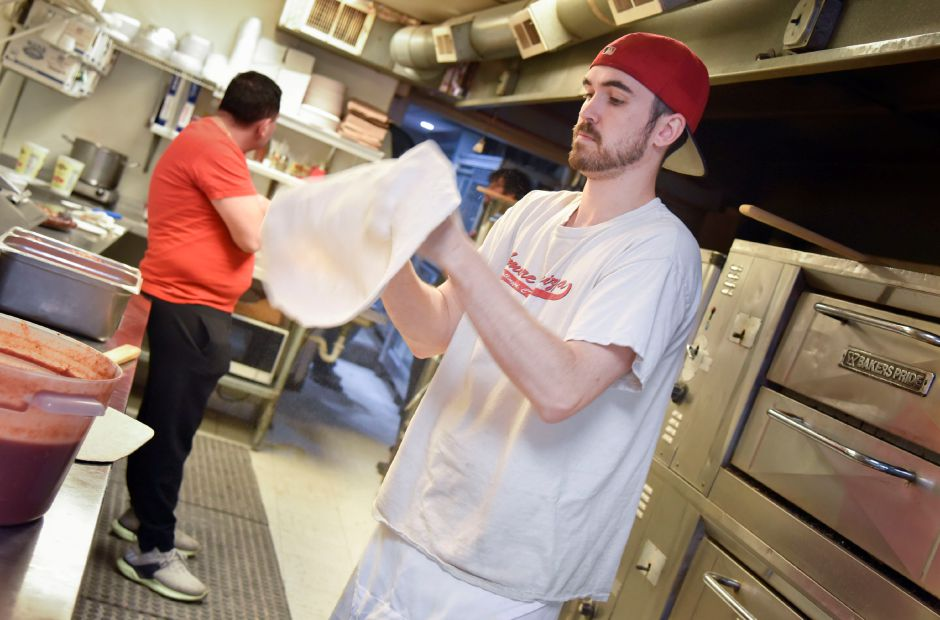 "Amore Apizza owner Eddie Conniff makes puts together some pizzas at his shop in Wallingford on Jan. 8, 2020. Amore Apizza is home to the ""buffaque,"" a stacked buffalo and barbecue pizza. 