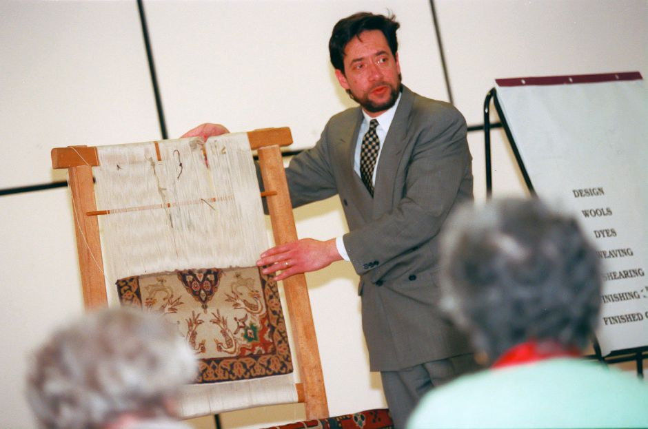 RJ file photo - Holding a partially woven run on a loom, John Balayan, a rug dealer with Araklian Rugs in New Haven, explains the intricate art of rug making at the Meriden Public Library, March 1999.