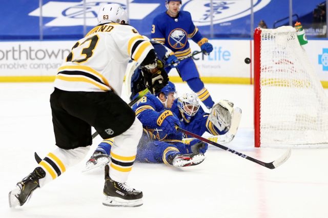 Boston Bruins forward Brad Marchand (63) puts the puck past Buffalo Sabres goalie Dustin Tokarski (31) during the first period of an NHL hockey game, Thursday, April 22, 2021, in Buffalo, N.Y. (AP Photo/Jeffrey T. Barnes)
