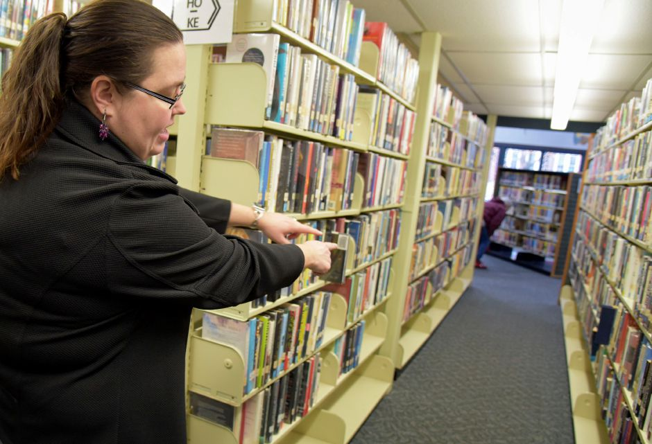 Library Executive Director Kristi Sadowski points to the narrow aisles in the Southington Public Library, 255 Main St., on Monday, Dec. 30, 2019. The town is looking to build a new, larger library to accomodate growing needs. | Bailey Wright, Record-Journal