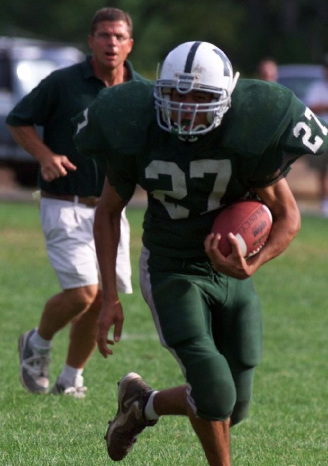 Maloney football coach Rob Szymaszek (in background) spurs on Maloney football player Edwin Roman during a scrimmage against Cheshire High School on Wednesday, Sept.1,1999.