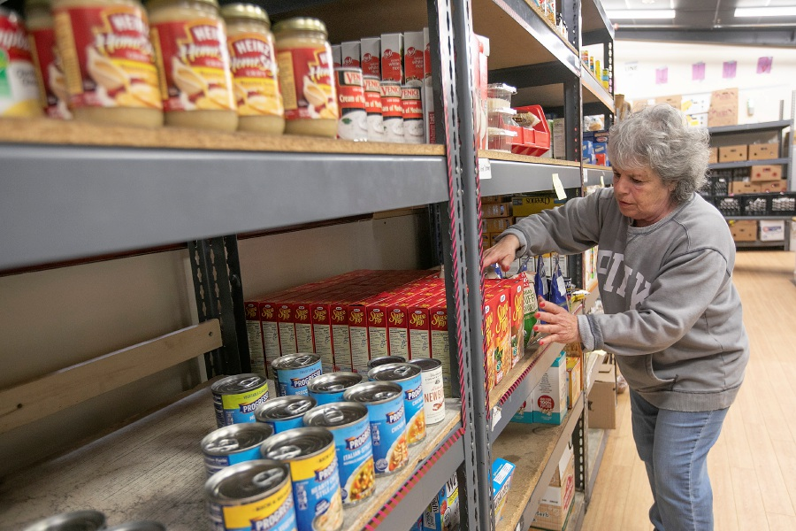 Jean Giglio, market place manager, straightens up food items on the shelves at Master