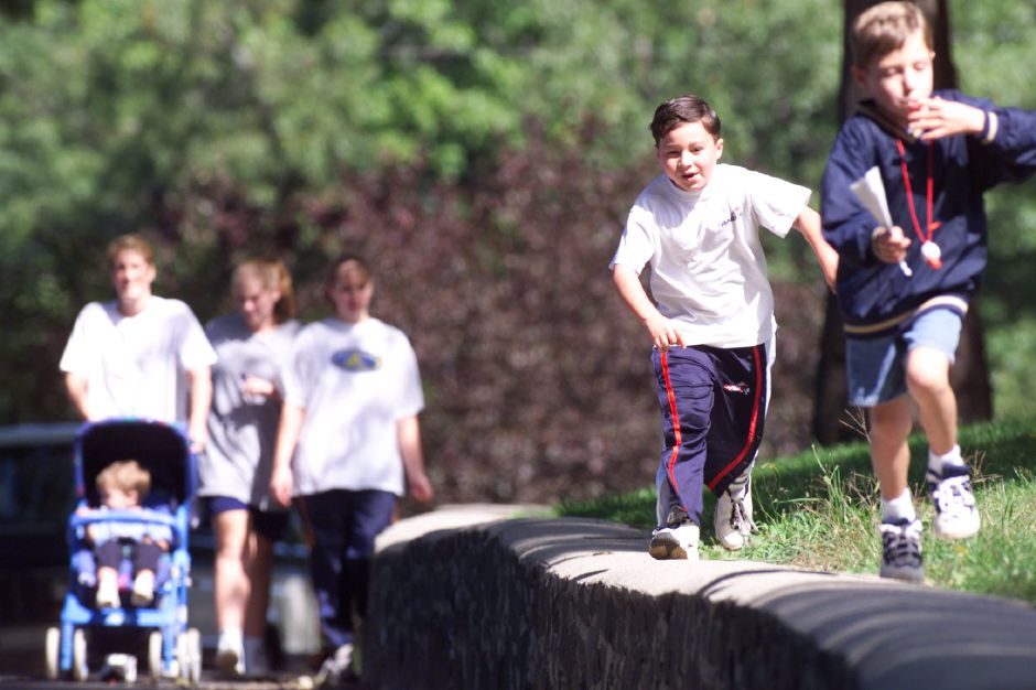Kindergarteners Christopher Amantea, 5 (far right) and his buddy Matthew Barre-Sanson, 5 race each other atop a low wall during the St. Joseph School Walk-a thon at Hubbard Park Sept. 26, 1999. Proceeds from the fund drive go to school activities.