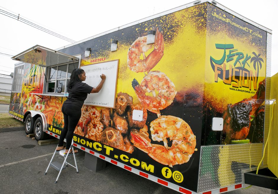 Enjoli Hassan, of Meriden, writes a message to customers on her Jamaican-fusion cuisine food truck stationed in the Wallingford Commons plaza across the street from Kohl