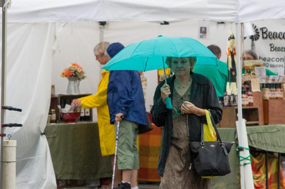 Judy Favale of Southington takes shelter under an umbrella Sunday during the Apple Harvest Festival in Southington October 8, 2017 | Justin Weekes / For the Record-Journal