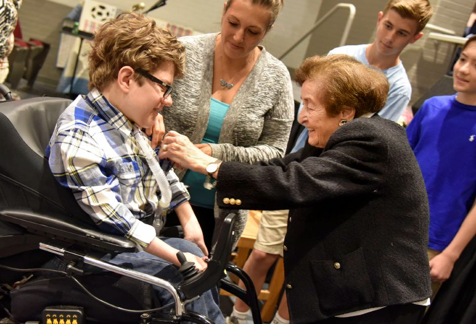 Holocaust survivor Judith Altmann gifts a piece of brick she saved from her time in the concentration camp Auschwitz to North Haven Middle School student Hunter Pageau after speaking to eighth-grade students on Friday.
