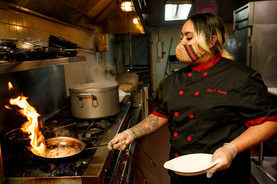 Chef Jaida Nieves cooks up a shrimp and garlic dish at Tata
