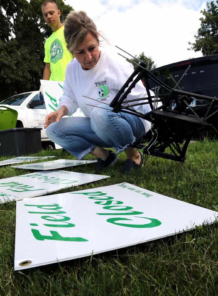 Dave Rodriguez looks on as Denis Stowik both from Wallingford, prepares signs to be placed around Choate Rosemary Hall as they get ready for the 35th annual TWIST soccer tournament on Friday August 16, 2019. Aaron Flaum, Record-Journal Staff