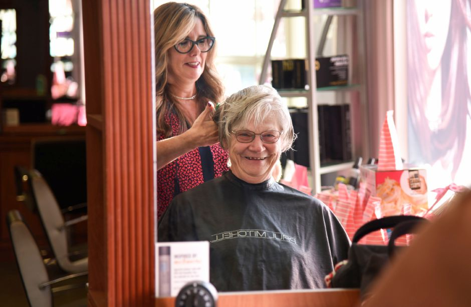 Sandy Derbacher, a breast cancer survivor from East Haven, gets her hair cut by North Haven salon owner Joyce-Lyn Altieri, on Wednesday at Flair for Hair. The salon is offering complementary hair treatments for cancer survivors through the month of October and will have the 20th annual Cutting for a Cure event on Oct. 28. Bailey Wright, Record-Journal