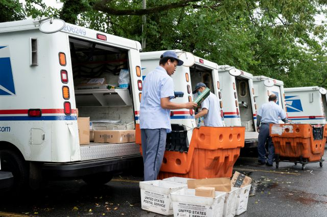 "FILE - In this July 31, 2020, file photo, letter carriers load mail trucks for deliveries at a U.S. Postal Service facility in McLean, Va. A U.S. judge on Thursday, Sept. 17, 2020, blocked controversial Postal Service changes that have slowed mail nationwide. The judge called them ""a politically motivated attack on the efficiency of the Postal Service"" before the November election. (AP Photo/J. Scott Applewhite, File)"