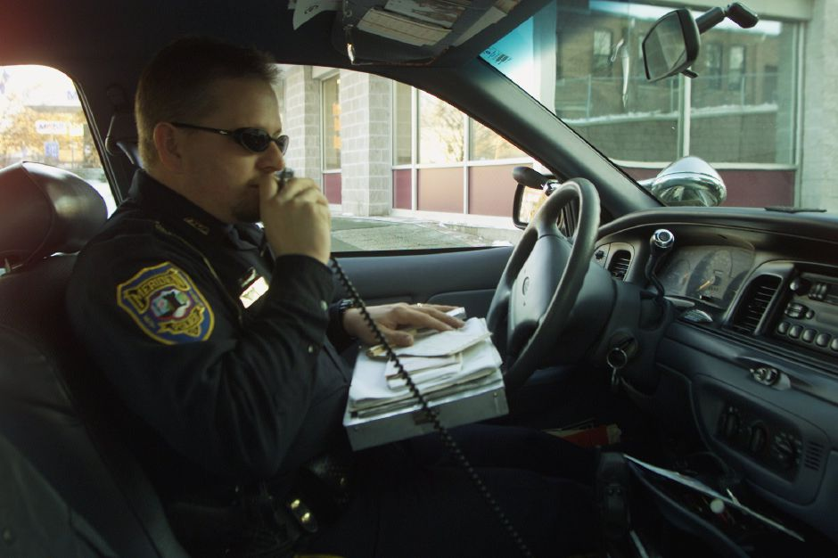During his patrol Tuesday afternoon, Meriden police officer Marc Lavoie calls in an infraction ( a motorist went through as red light at the intersection of Broad and East main Streets) Jan. 23, 2001.