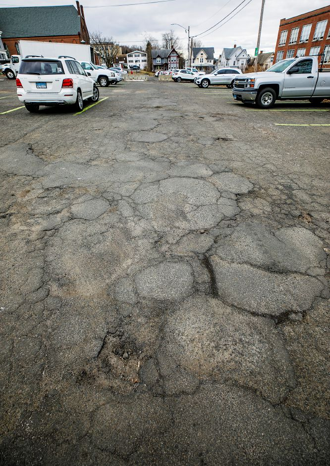 Cracked pavement in the Simpson Court rear parking lot in Wallingford, Fri., Jan. 22, 2021. The Town Council is scheduled to revisit the proposal for parking lot improvements behind Simpson Court businesses and Wallace Avenue at its meeting Tuesday. Dave Zajac, Record-Journal