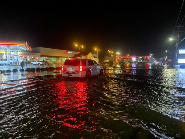 A car is driven along water-covered Sea Mountain Highway in North Myrtle Beach, S.C., as Isaias neared the Carolinas on Monday night, Aug. 3, 2020. (Jason Lee/The Sun News via AP)