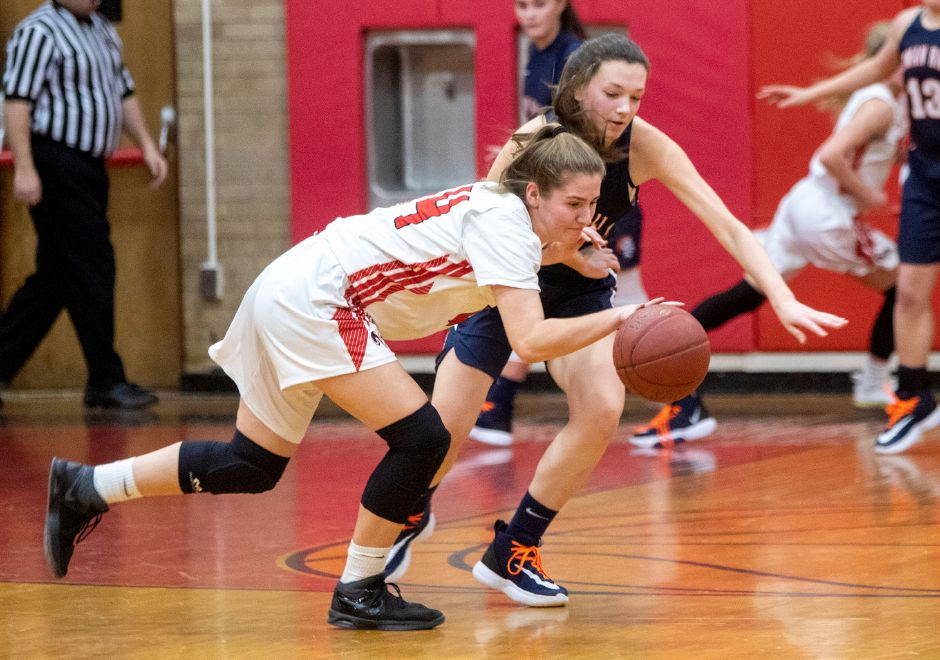 Cheshire's Rylee Post keeps the ball away from Lyman Hall's Natalie Panagrosso during the first half at the Cheshire High School East Gym on Tuesday, January 21, 2020. Aaron Flaum, Record-Journal