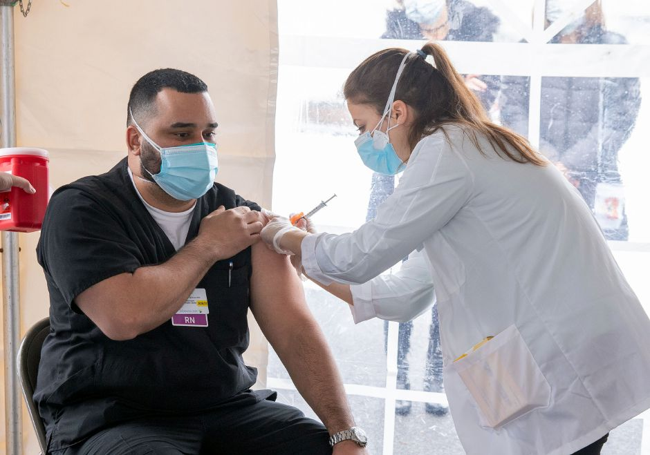 CVS Pharmacist Bionca Malaspina gives the Pfizer BioNTech COVID-19 Vaccine to Luis Figueroa Ortiz, a nurse at Masonicare, during a celebration of the roll-out for the COVID-19 vaccination in front of the Sturges Building at the Masonicare Facility in Wallingford on Friday, December 18, 2020. Aaron Flaum, Record-Journal