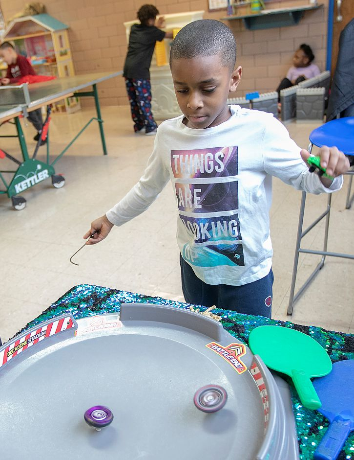 Azyion Cannon, 7, of Meriden, sends a set of Beyblades spinning while enjoying part of his week off from school at the Boys and Girls Club.