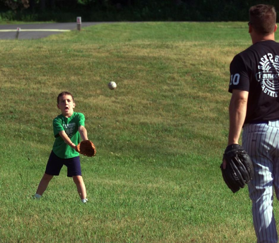 Matthew Burdette, 7, has a quick game of catch with his father Tom Burdette at the Southington YMCA