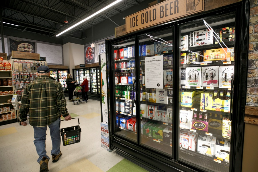 A customer passes by a selection of beers at Tops Marketplace in Southington, Wed., Feb. 24, 2021. Local wineries and liquor stores are responding to a bill that, if passed, would allow grocery stores in Connecticut to begin selling wine. Dave Zajac, Record-Journal