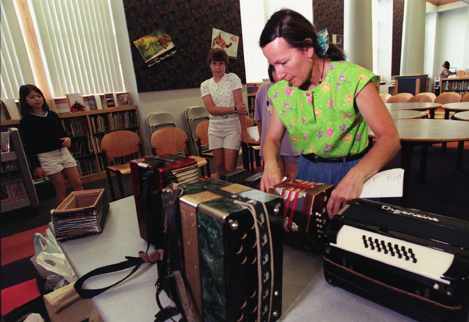Mary Morse (right) of Marlborough performed and showed off her accordian collection at the John Barry satellite branch of the Meriden Public Library. In the backround ( left to right) are Megan Wollschlager,13 of Cheshire, Susan Burgess,13 and her sister Amy Burgess,11 of Meriden July 14, 1999.