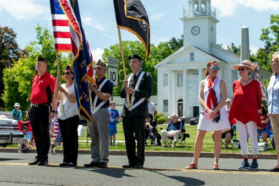 Flag bearers stand at attention in front of the veterans memorial next to the Cheshire Town Hall during the town