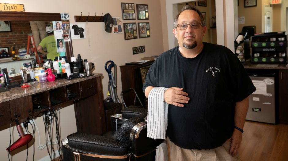 "Above, Wallingford resident Dino Fernicola, seen here on Wednesday, owns  Dino's Modern Barbershop. He estimated that each barber went from seeing between 15 to 20 clients a day to around 10 to 15. He increased the price of haircuts by $2. ""Your output is changed completely in terms of how many haircuts you do in a day,"" he said."