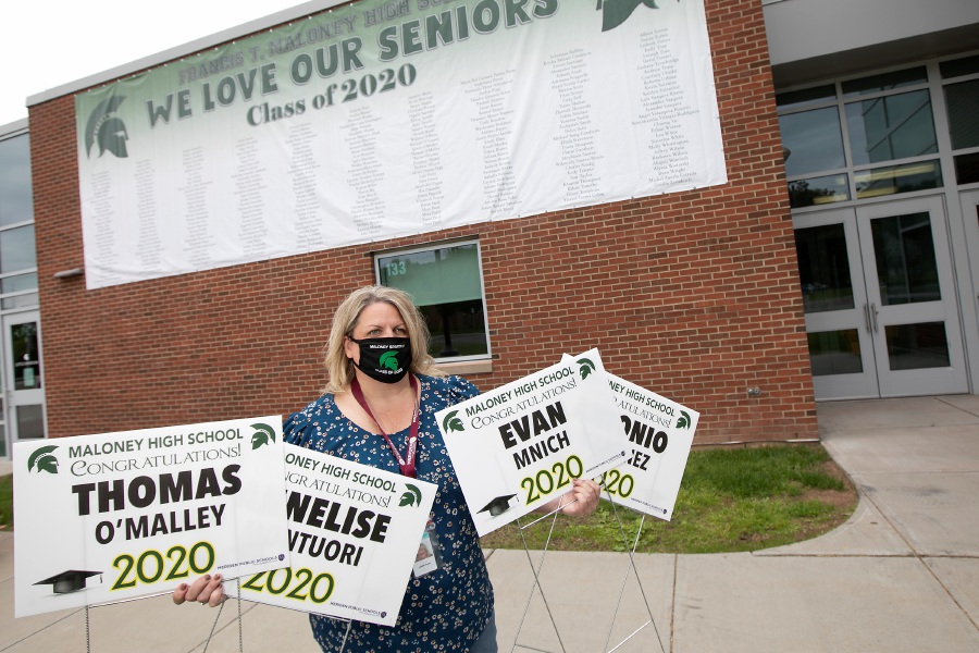 Principal Jennifer Straub dons the new Maloney Spartans Class of 2020 mask Tuesday while holding lawn signs available for each graduate under a new banner at Maloney High School in Meriden. School officials finalized graduation plans. Dave Zajac, Record-Journal