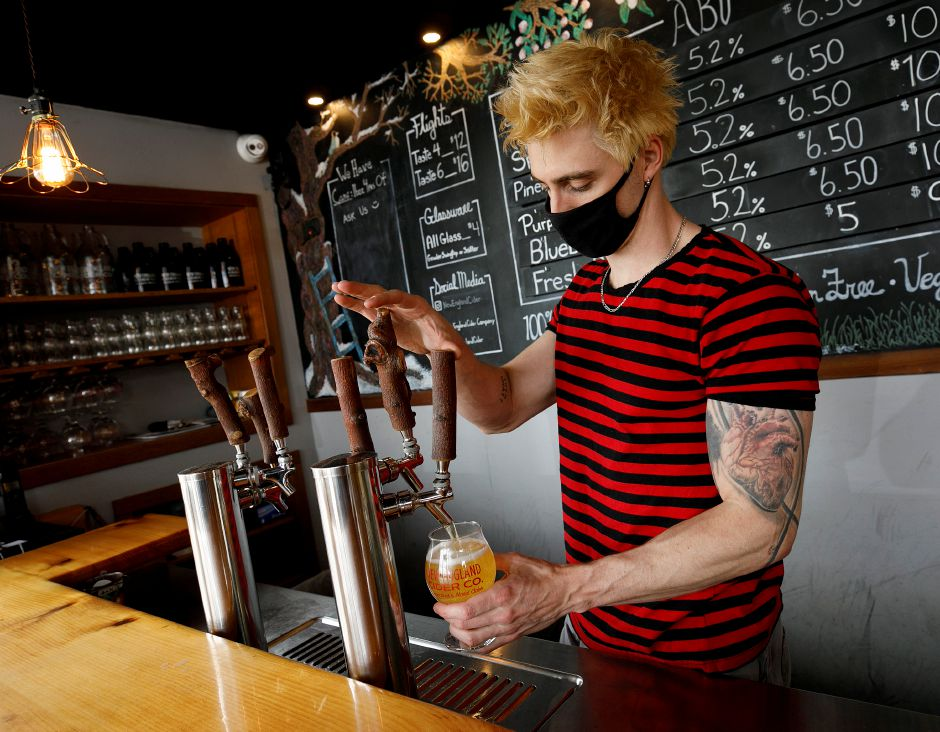 Bar Manager Dan Hill pours a strawberry cider on Wednesday at New England Cider Company, 110 N. Plains Industrial Road, Wallingford. Dave Zajac, Record-Journal