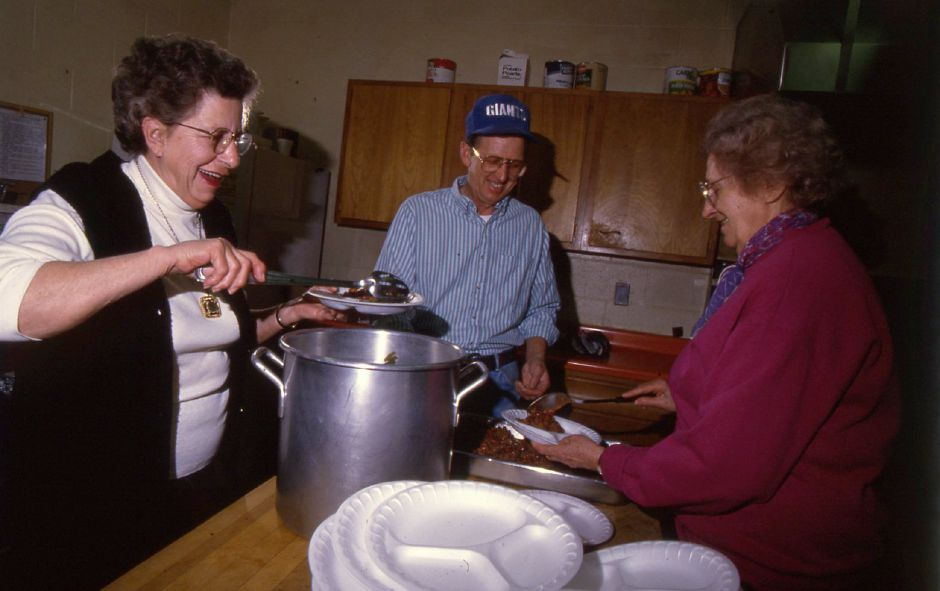 RJ file photo - The Holy Angels kitchen crew from left, Rita Pouliot, Ed McCray and Halen Maslar dish up lunches at the Soup Kitchen in Meriden Jan. 24, 1994.