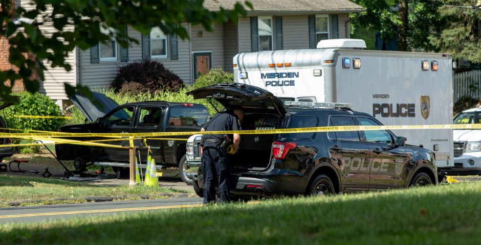 A Meriden Police officer retrieves police tape from a cruiser outside 115 Allen Avenue in Meriden, where a fatal shooting occurred on August 11, 2019. | Devin Leith-Yessian/Record-Journal