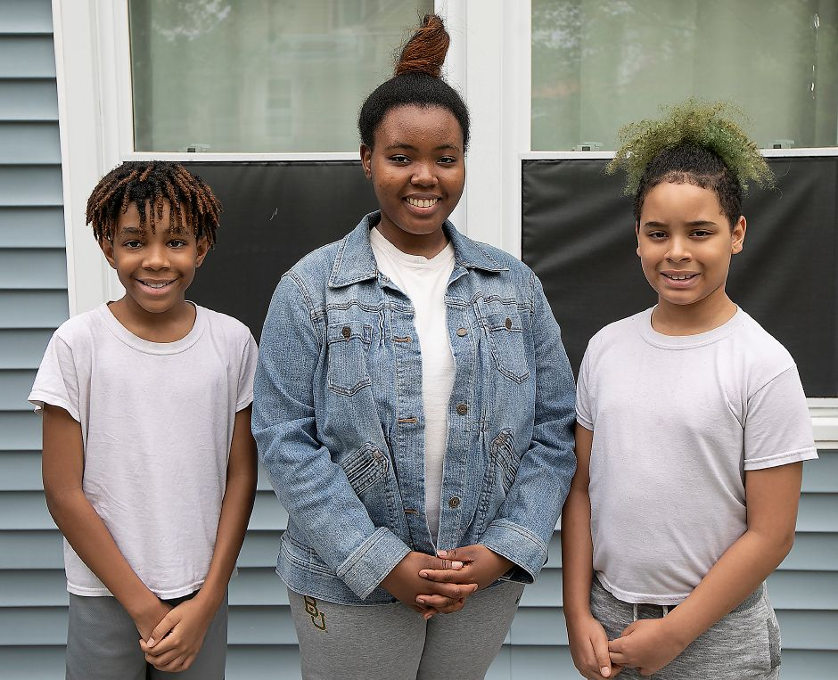 Left to right, Zaire Evans, 11, Sariah Royal, 17, and Tristan Smith, 10, smile in the backyard of their Meriden residence, Fri., May 29, 2020. AT&T donated 100 smartphones to children in the Nutmeg Big Brothers Big Sisters program to make the virtual mentoring program more enjoyable and help them stay connected with their mentor. Dave Zajac, Record-Journal