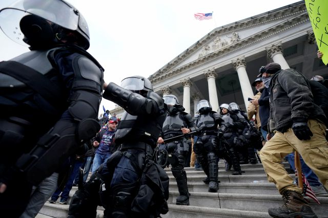Police in riot gear walk out of the Capitol, Wednesday, Jan. 6, 2021, in Washington. As Congress prepares to affirm President-elect Joe Biden