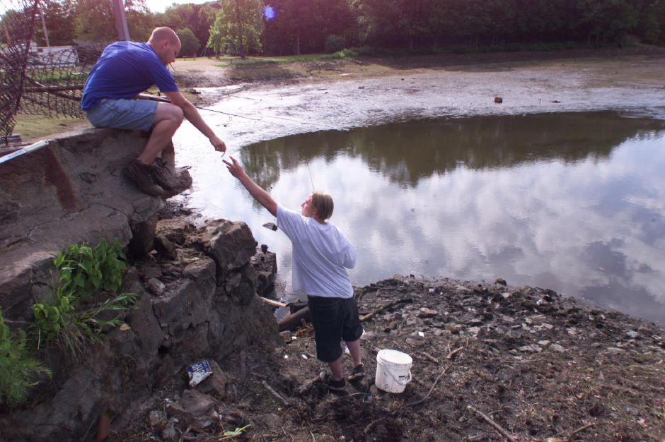 RJ file photo - David Lord,23 hands a fishing lure to younger brother Timothy Lord,18 as they fish Black Pond Wednesday morning June 16, 1999. The men are moving fish from the drained pond to safer waters.
