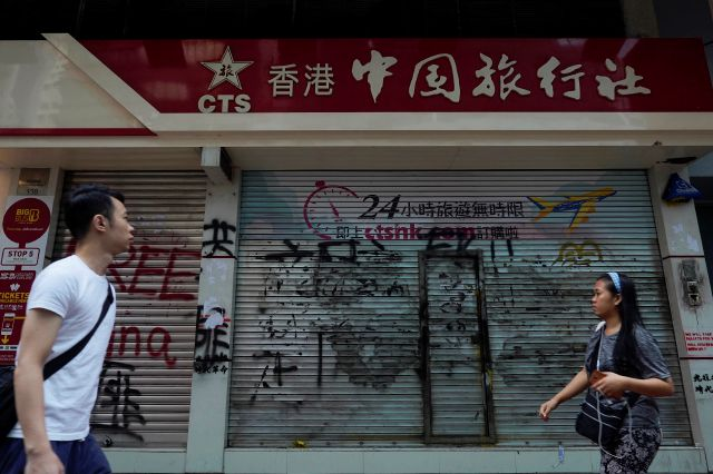 Pedestrians look at graffiti in front of China Travel Service in Hong Kong, Monday, Oct. 7, 2019. Tens of thousands of masked protesters marched defiantly in the city center Sunday, but the peaceful rallies quickly degenerated into chaos at several locations as hard-liners again lobbed gasoline bombs, started fires and trashed subway stations and China-linked banks and shops. (AP Photo/Vincent Yu)