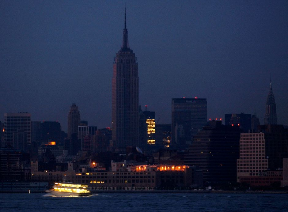 The Empire State building in midtown New York City is dark with a few lights on in surrounding buildings as a ferry passes on the Hudson River as seen from Jersey City, N.J., Thursday, Aug. 14, 2003. (AP Photo/Mike Derer)