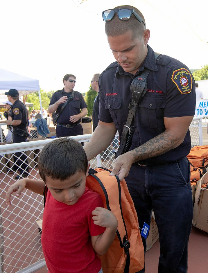 Firefighter Anthony Boscarino of Engine 2 helps Aidan Cortes, 6, of Meriden with his new backpack during the Meriden Fire Local 1148 annual Back-to-School Expo on the Meriden Green, Tues. Aug. 20, 2019. Dave Zajac, Record-Journal