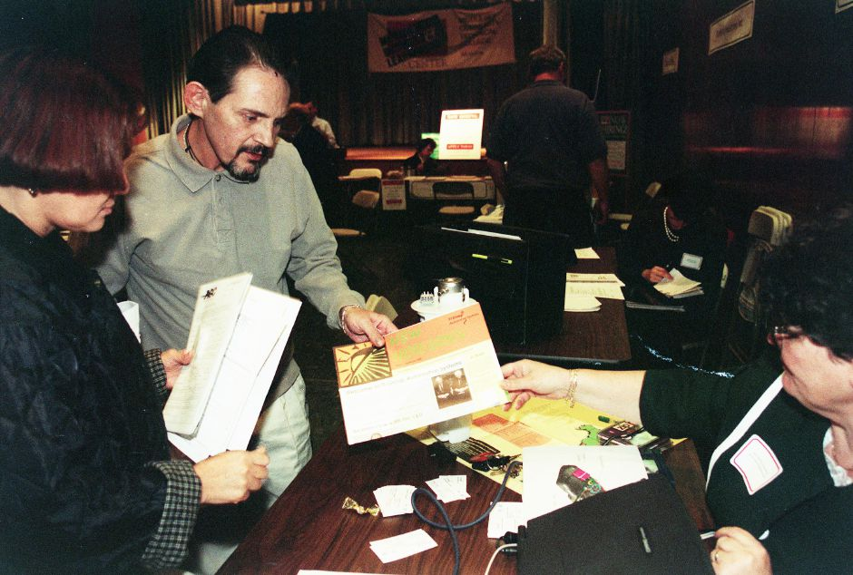 Hector Agostini and Zaida Melendez of Meriden and a former employees of Napier attended the job fair at the Meriden Buisness and Learning Center Oct. 28, 1999. The two were employed in the casting department at Napier and were looking for new employment due to the shutdown of Napier. Maureen T. Seaburgh gives the two information about TI Group Automotive Systems.