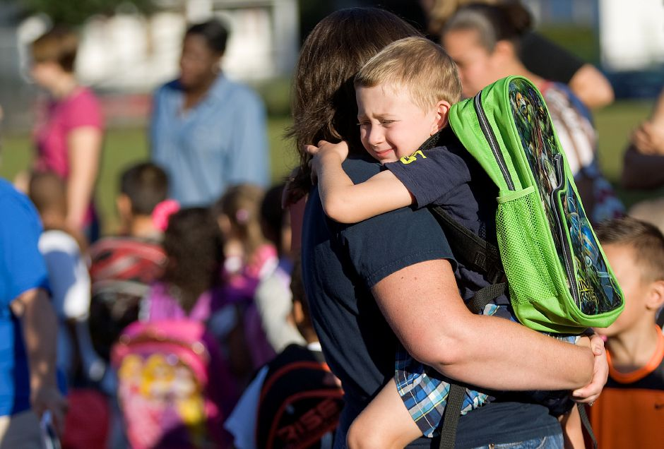Zachary Crispino, 4, of Meriden, clings to mother, Karri, prior to the first day of extended-day kindergarten at Roger Sherman Elementary School in Meriden, Wednesday, August 27, 2014. Students now attend the school for an additional 100 minutes per day, using the extra time for more hands-on enrichment activities. | Dave Zajac / Record-Journal