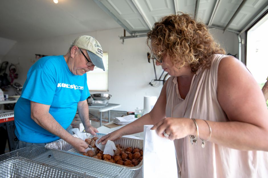 Angelo Lasterina, left, prepares apple fritters during his grandson